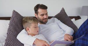 Ojca i syna lying on the beach na opowieść rezerwuje w sypialni 4k w domu zbiory wideo