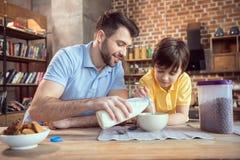 Ojca i syna narządzania czekoladowe kukurydzane piłki z mlekiem Obraz Stock
