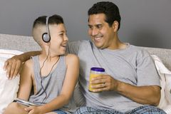 Ojca i syna obsiadanie na łóżkowym słuchaniu muzyka obraz royalty free