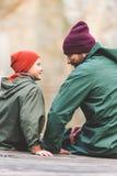 Ojca i syna obsiadanie na drewnianym moscie Obraz Stock