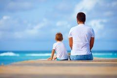 Ojca i syna obsiadanie na molu blisko morza Fotografia Stock