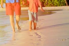 Ojca i syna odprowadzenie na plażowym opuszcza odcisku stopy Zdjęcia Stock