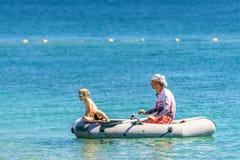 Ojca i syna pławik wpólnie w gumowej łodzi na Czarnym Dennym wybrzeżu na pogodnym letnim dniu zdjęcia stock