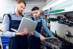 Ojca i syna praca przy auto usługa Dwa mechanika pracują z szczegółami samochód Fotografia Royalty Free