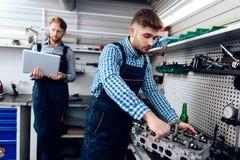 Ojca i syna praca przy auto usługa Dwa mechanika pracują z szczegółami samochód Zdjęcia Royalty Free