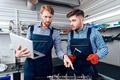 Ojca i syna praca przy auto usługa Dwa mechanika pracują z szczegółami samochód Obrazy Royalty Free