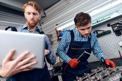 Ojca i syna praca przy auto usługa Dwa mechanika pracują z szczegółami samochód Obrazy Stock