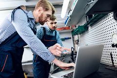 Ojca i syna praca przy auto usługa Dwa mechanika pracują z szczegółami samochód Obraz Stock