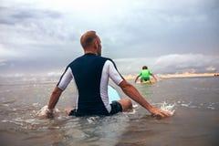 Ojca i syna surfingowowie pokonujący machają na kipieli linii zdjęcia royalty free