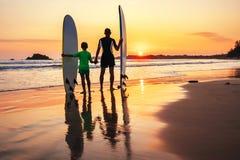 Ojca i syna surfingowowie spotykają zmierzch na ocean plaży Obrazy Stock