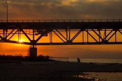 Ojca i syna sylwetki odprowadzenie na plaży pod Mackinaw mostem przy zmierzchem zdjęcia stock