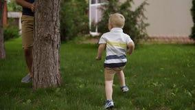 Ojca i syna sztuka chuje aport wokoło drzewa - i - Mała blondynki chłopiec biega szczęśliwy czas rodzicielstwo Zielona trawa woko zbiory