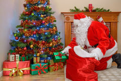 Ojca kładzenia Bożenarodzeniowi prezenty pod drzewem Zdjęcia Royalty Free