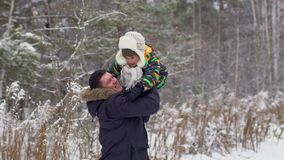 Ojca miotania syn w powietrzu, zwolnione tempo Ojciec i syn ma zabawę w zima parku, ojca miotania młoda chłopiec up w zdjęcie wideo