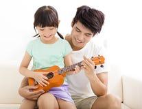 Ojca nauczania córka Bawić się ukulele Obraz Royalty Free