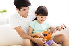 Ojca nauczania córka Bawić się ukulele Zdjęcia Stock