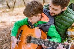 Ojca nauczania syn bawić się gitarę Fotografia Royalty Free