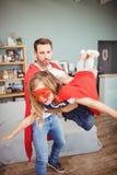 Ojca przewożenia córka jest ubranym bohatera kostium zdjęcie stock