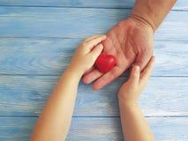 Ojca ` s dzień Wręcza tata i dziecka trzyma dziękczynnego serce na Błękitnym Drewnianym tle Zdjęcie Royalty Free