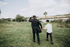 Ojca syn iść łąkowy wpólnie jeziora czerń obrazy stock