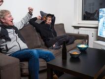 Ojca, syna i kota dopatrywania pucharu świata futbolowa piłka nożna na tv, fotografia stock