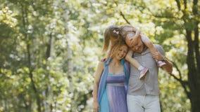 Ojciec - śmiały mężczyzna, matka - blondynki mała dziewczynka i - chodzący w parku przy słonecznym dniem Zdjęcia Royalty Free