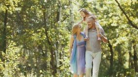 Ojciec - śmiały mężczyzna, matka - blondynki mała dziewczynka i - chodzący w parku przy słonecznym dniem Obraz Stock