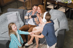 Ojciec Bierze fotografię córki I syna Słuchająca Dancingowa muzyka W hełmofonach, Szczęśliwy Uśmiechnięty Rodzinny obsiadanie Na  Zdjęcia Royalty Free