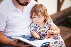 Ojciec czyta jego berbecia dzieciak, plenerowy zdjęcie royalty free
