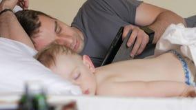 Ojciec czyta wiadomość na pastylce blisko sypialnego dziecka Chłopiec odpoczywa w przedpolu dom na łóżku zbiory wideo