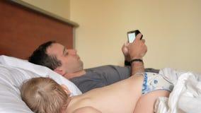 Ojciec czyta wiadomość na pastylce blisko sypialnego dziecka Chłopiec odpoczywa w przedpolu dom na łóżku zdjęcie wideo