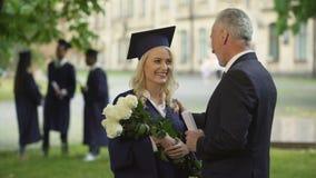 Ojciec daje kwiatom jego absolwent córki, gratulacje, poojcowska duma zbiory