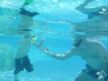 ojciec gestykuluje akwalungu syna nauczanie zdjęcie stock
