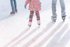 Ojciec i córka jeździć na łyżwach na lodowisku podczas zima wakacji zdjęcia stock