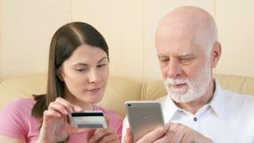 Ojciec i córka robi zakupy online z kredytową kartą na smartphone Technologii use starymi ludźmi zbiory wideo