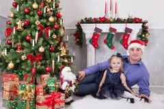 Ojciec i córka siedzimy blisko choinki Ojciec S Fotografia Stock