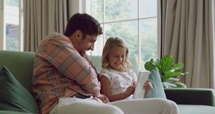Ojciec i córka używa cyfrową pastylkę na kanapie 4k w domu zdjęcie wideo