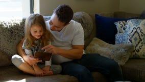 Ojciec i córka używa cyfrową pastylkę w żywym pokoju 4k zbiory wideo