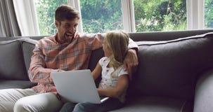 Ojciec i córka używa laptop na kanapie 4k w domu zdjęcie wideo