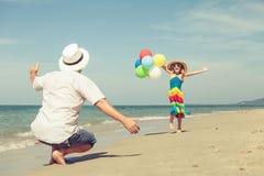 Ojciec i córka z balonami bawić się na plaży przy da Zdjęcia Royalty Free