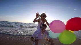 Ojciec i córka z balonami bawić się na plaży przy zmierzchu czasem zdjęcie wideo