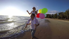 Ojciec i córka z balonami bawić się na plaży przy zmierzchu czasem zbiory wideo