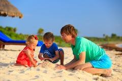 Ojciec i dwa dzieciaka bawić się z piaskiem na plaży Zdjęcia Stock