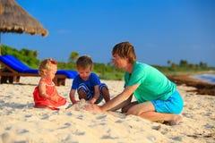 Ojciec i dwa dzieciaka bawić się z piaskiem na plaży Obrazy Royalty Free