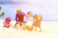 Ojciec i dwa dzieciaka bawić się z piaskiem na plaży Obrazy Stock