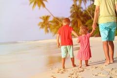 Ojciec i dwa dzieciaka chodzi na lecie wyrzucać na brzeg zdjęcia royalty free