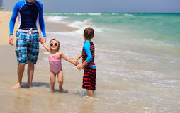 Ojciec i dwa dzieciaka chodzi na plaży zdjęcia royalty free
