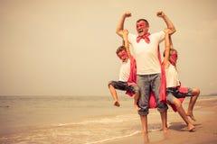 Ojciec i dzieci bawić się bohatera na plaży przy dnia ti fotografia stock