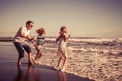 Ojciec i dzieci bawić się na plaży przy dnia czasem Concep Obrazy Stock