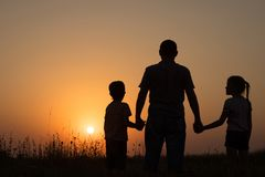Ojciec i dzieci bawić się w parku przy zmierzchu czasem Fotografia Stock